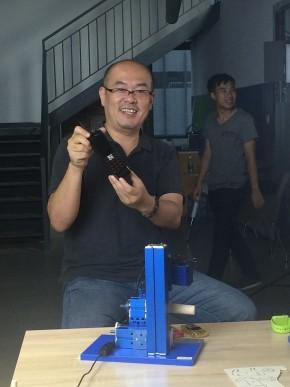 David Li holding a large battery phone at SZOIL